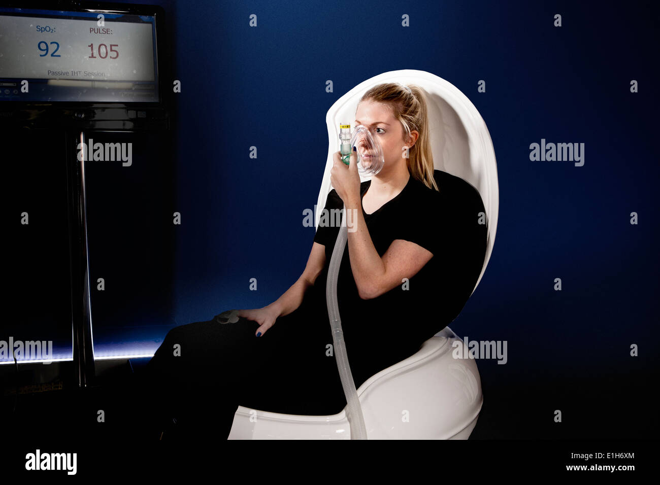 Young woman using face mask in gym altitude centre - Stock Image