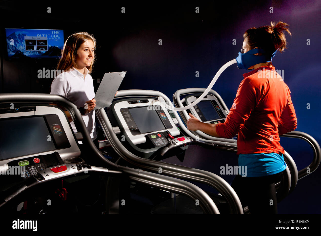 Trainer monitoring mid adult woman with face mask on gym treadmill in altitude centre - Stock Image
