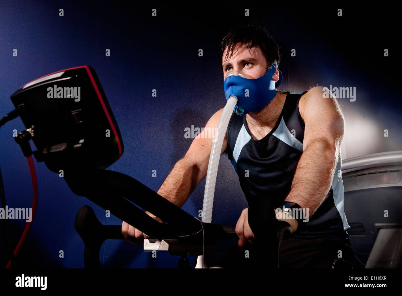 Mid adult man in face mask on gym exercise cycle in altitude centre - Stock Image