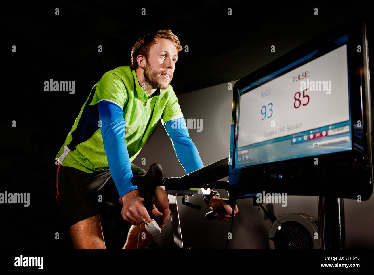 Young man on gym exercise cycle in altitude centre - Stock Image