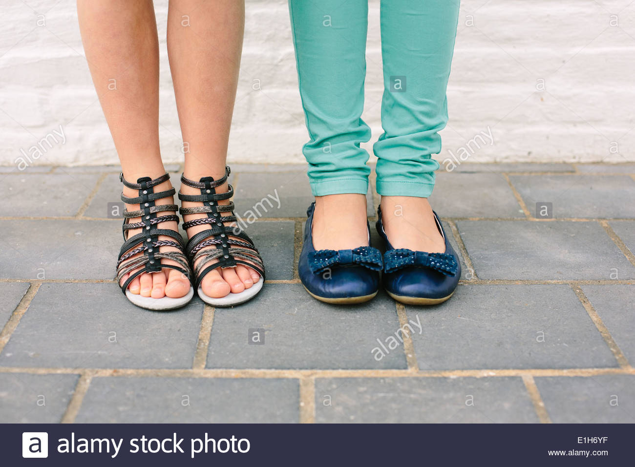 Close up of two sisters legs and footwear - Stock Image