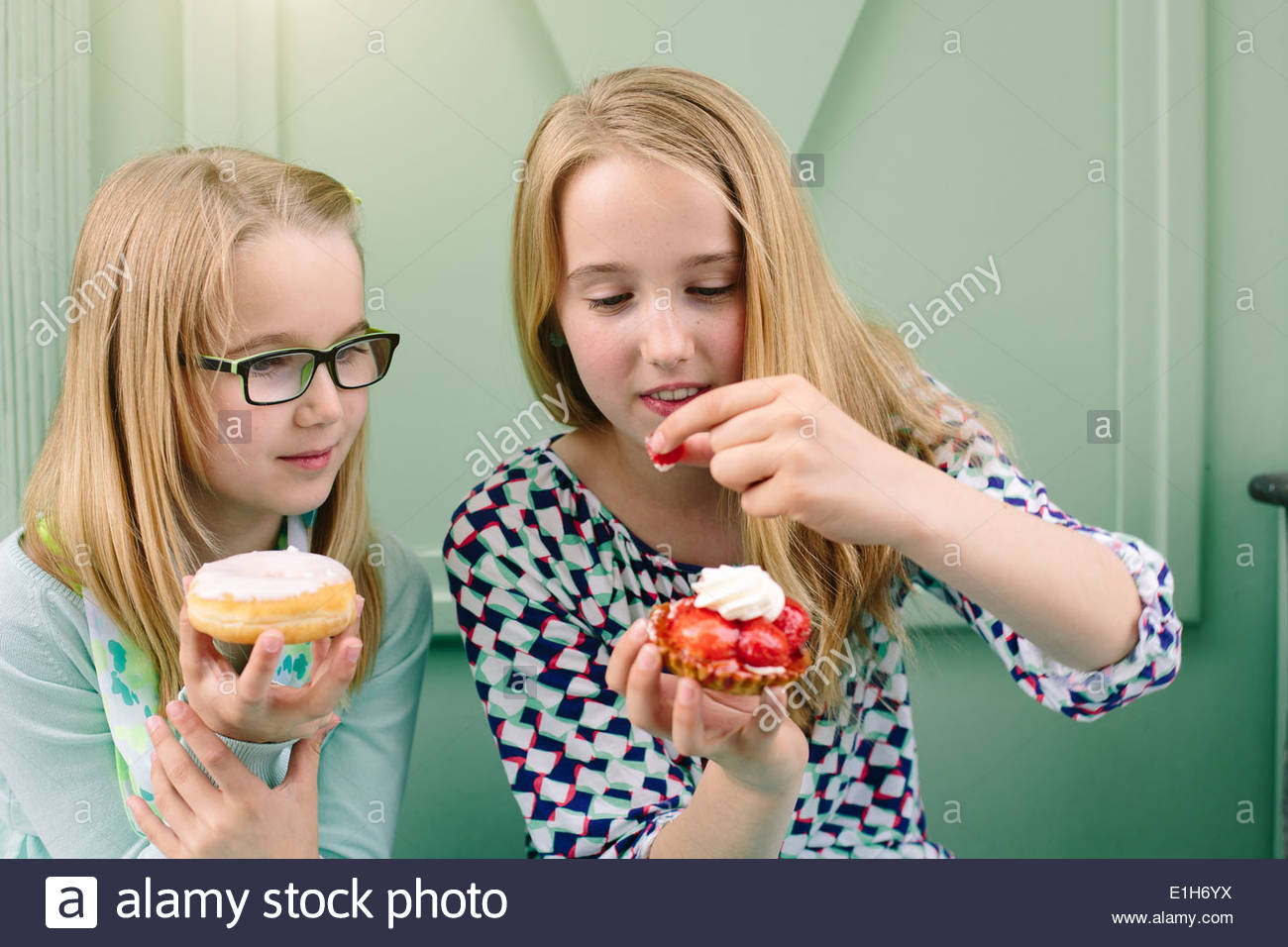 Two sisters holding cakes and strawberry - Stock Image
