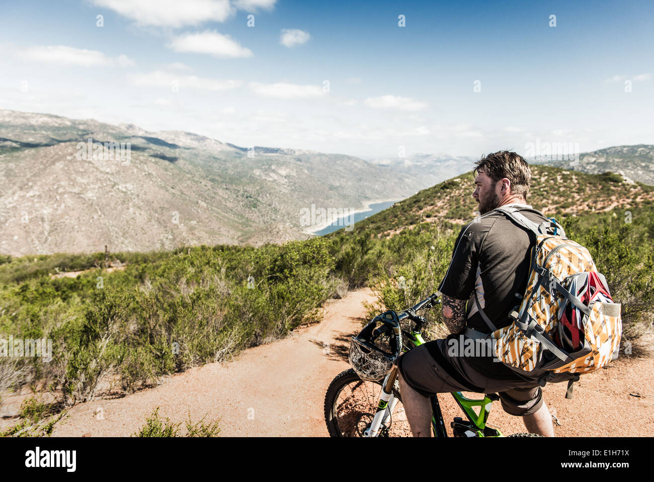 Downhill mountain biker looking at view Stock Photo