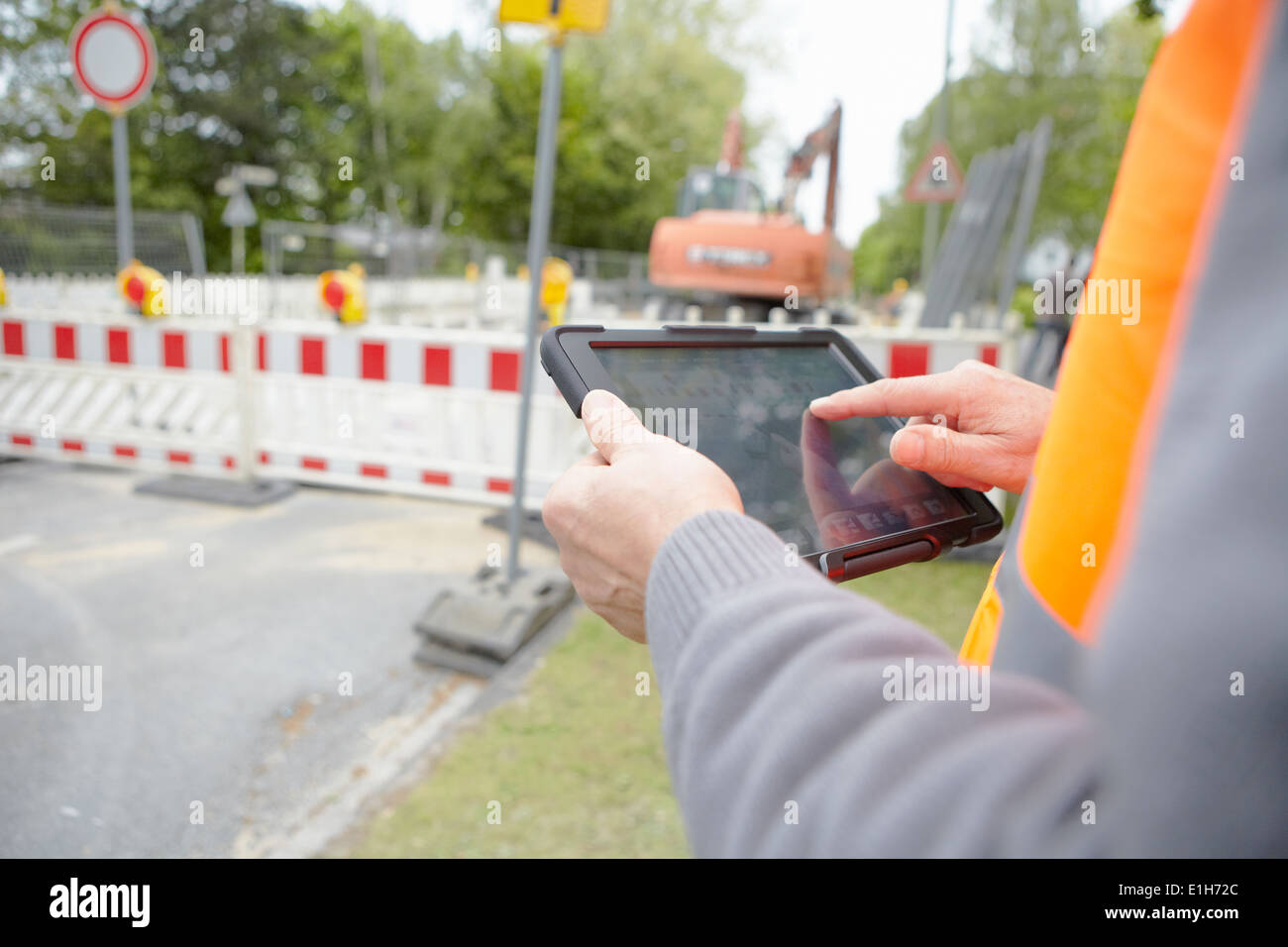 Close up of foremans hands using digital tablet on road construction site - Stock Image