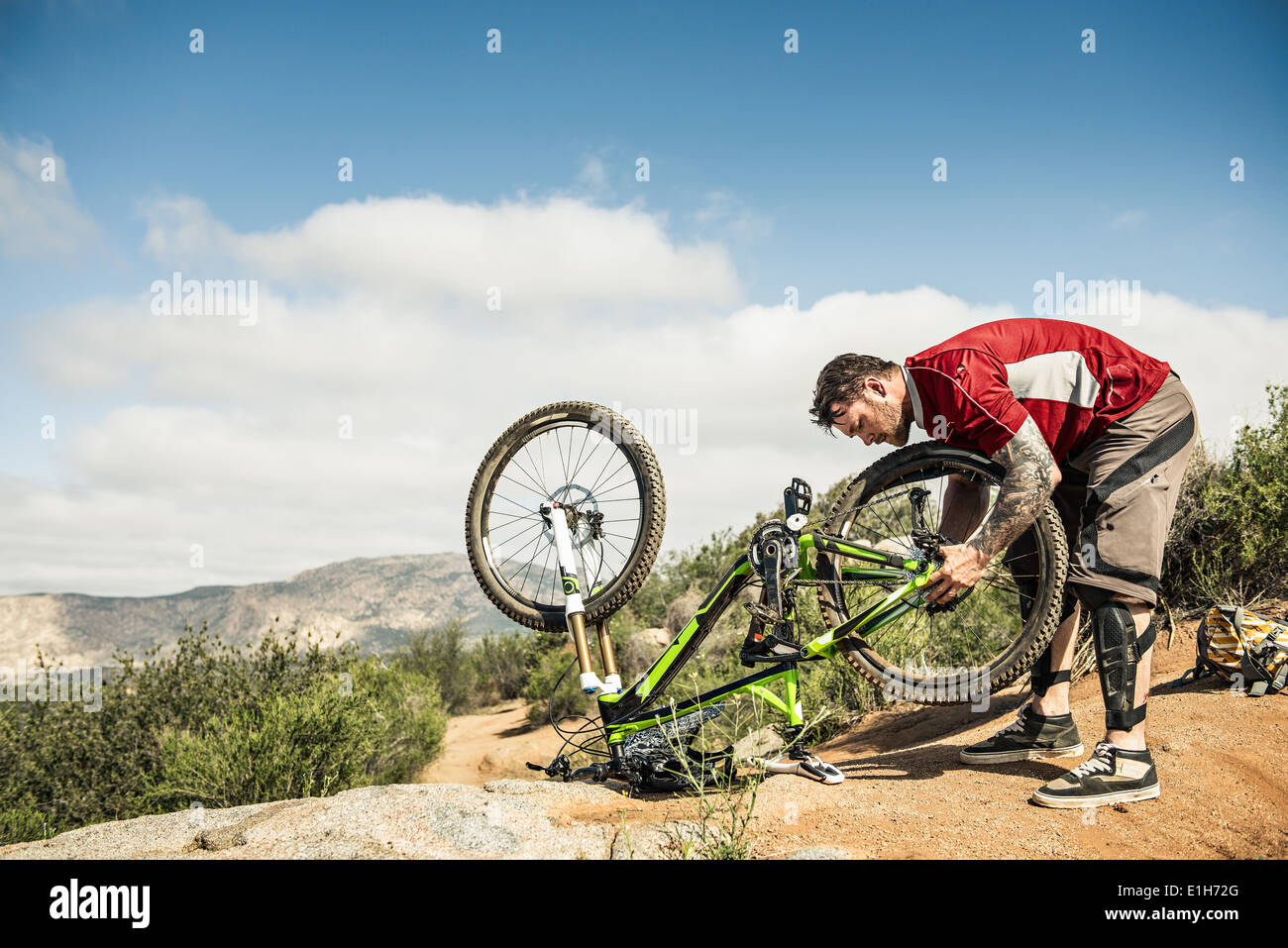 Downhill mountain biker fixing bike - Stock Image