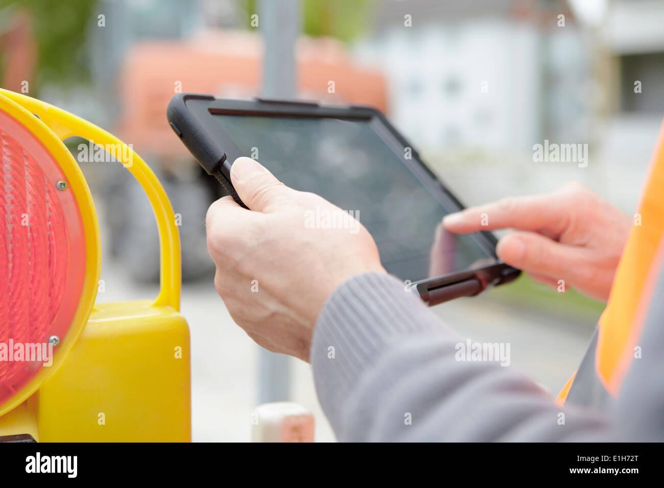 Foremans hands using digital tablet on road construction site - Stock Image