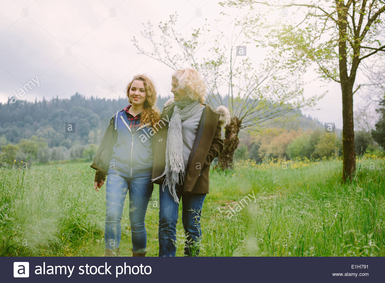 Mature woman and teenage daughter strolling in field - Stock Image