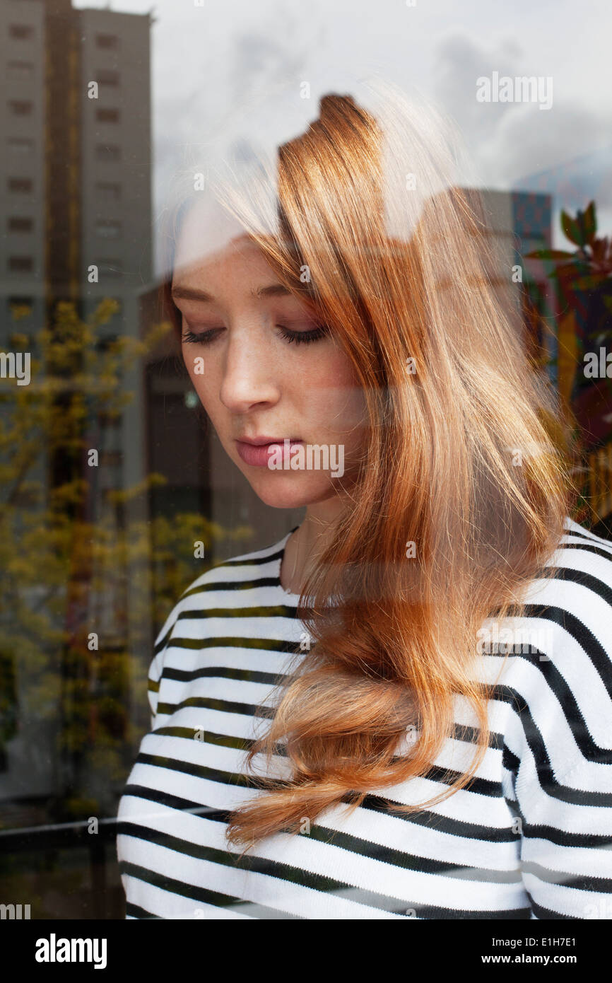 Young woman through window - Stock Image