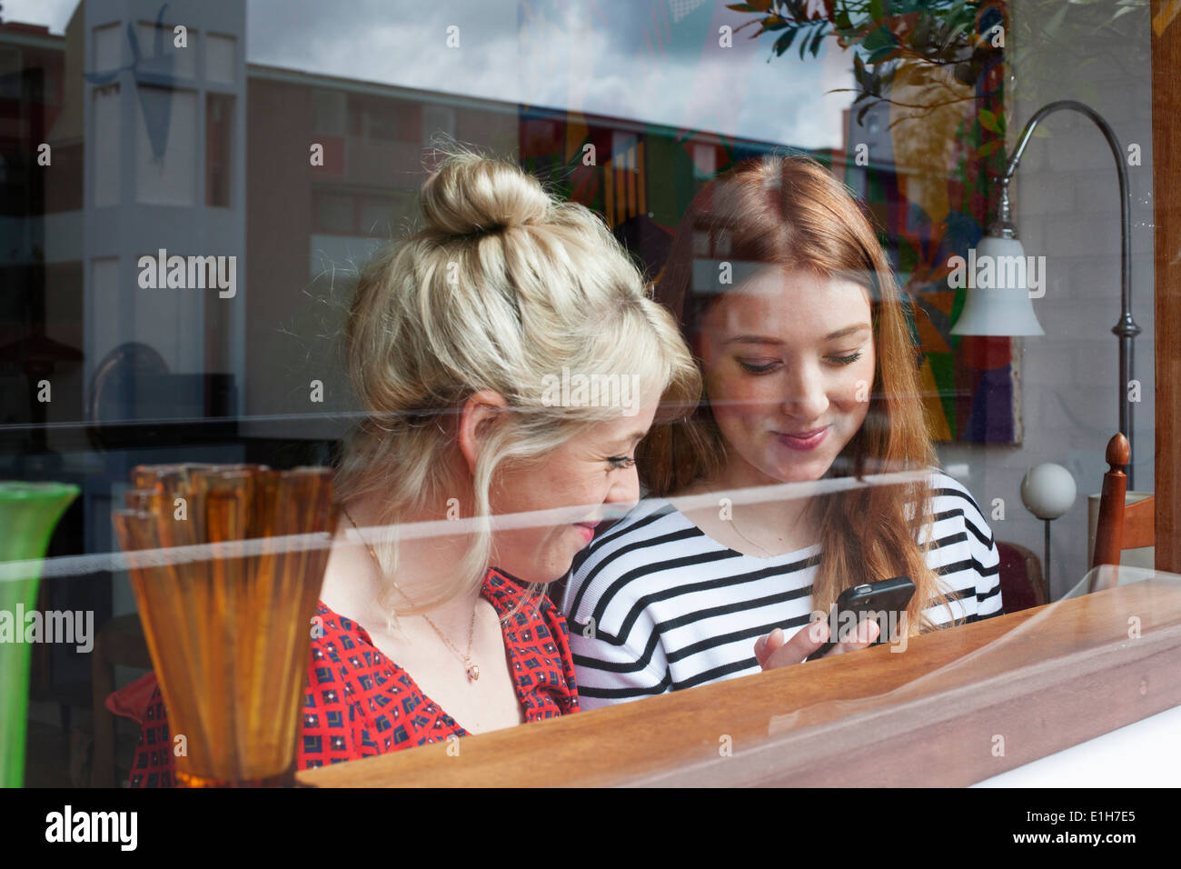 Young women through window, looking at smartphone Stock Photo