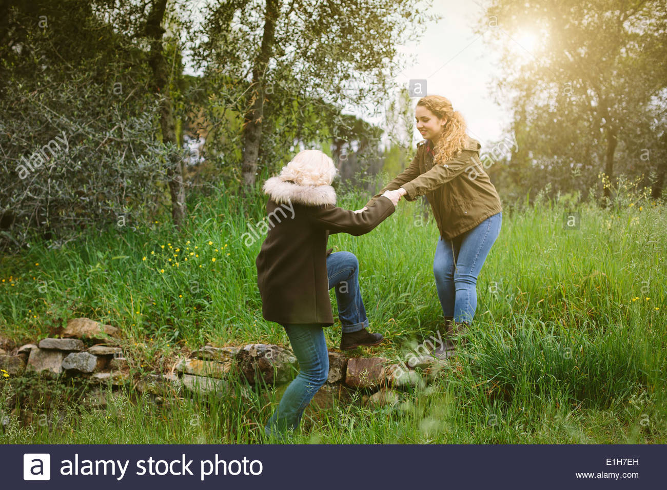 Teenage girl helping her mother over a stone wall - Stock Image