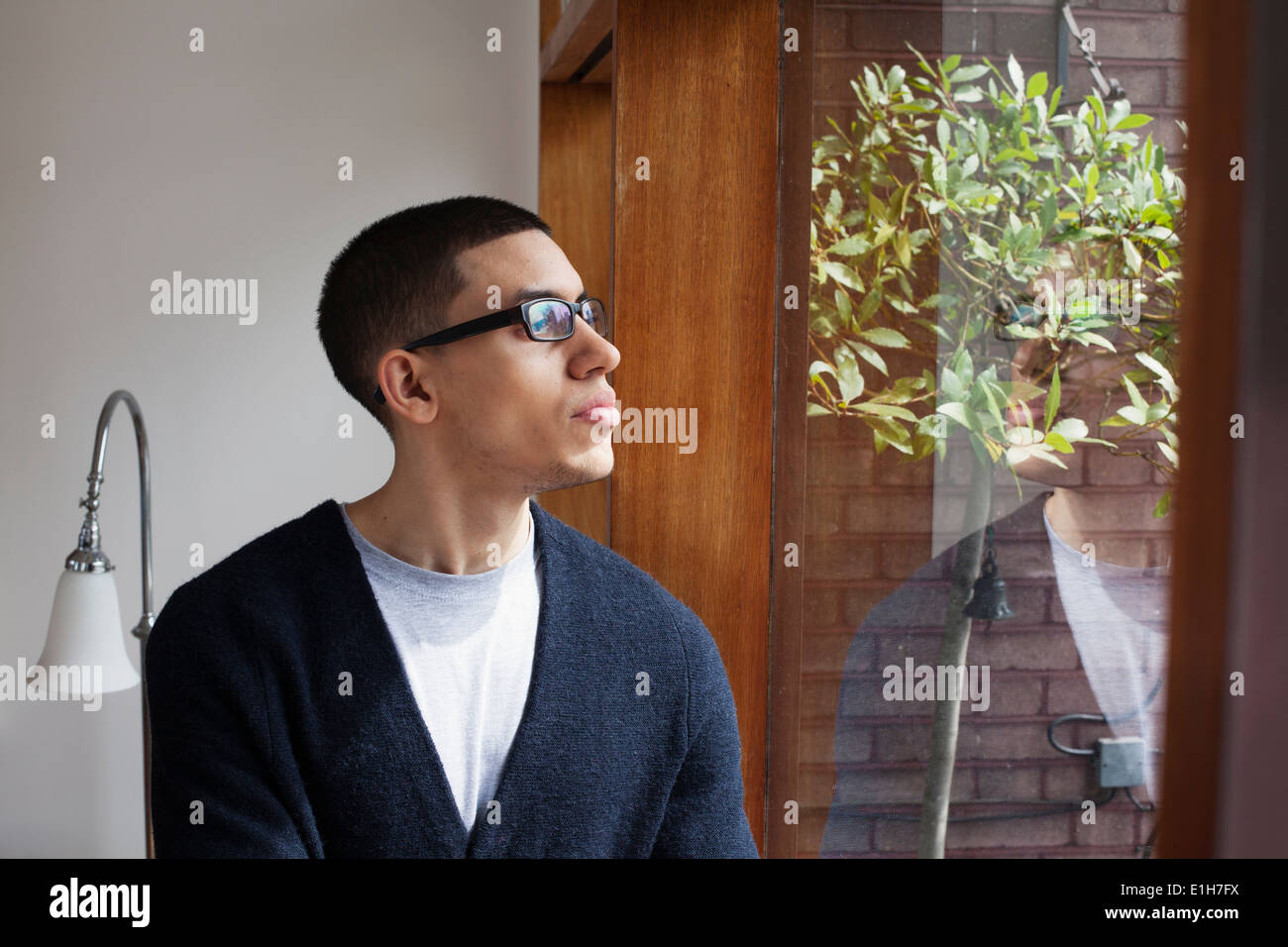 Young man looking through window - Stock Image