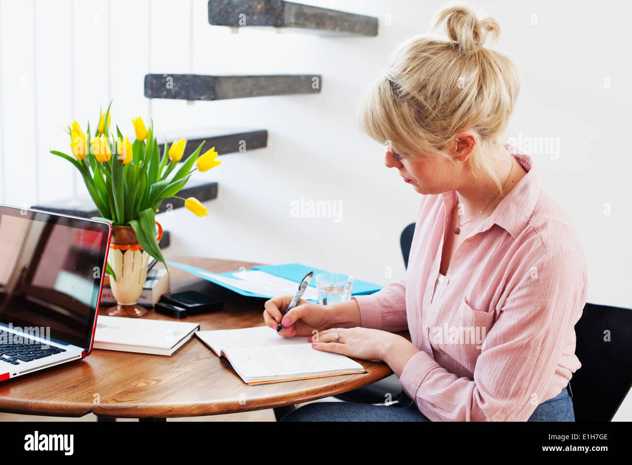 Young woman sitting at table writing - Stock Image