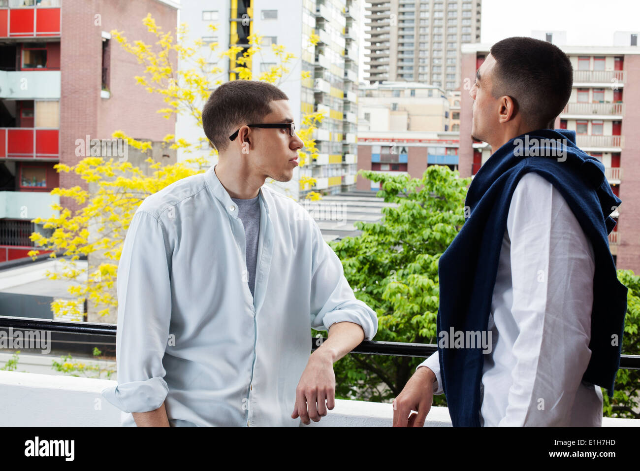 Young men standing on balcony in London, UK - Stock Image