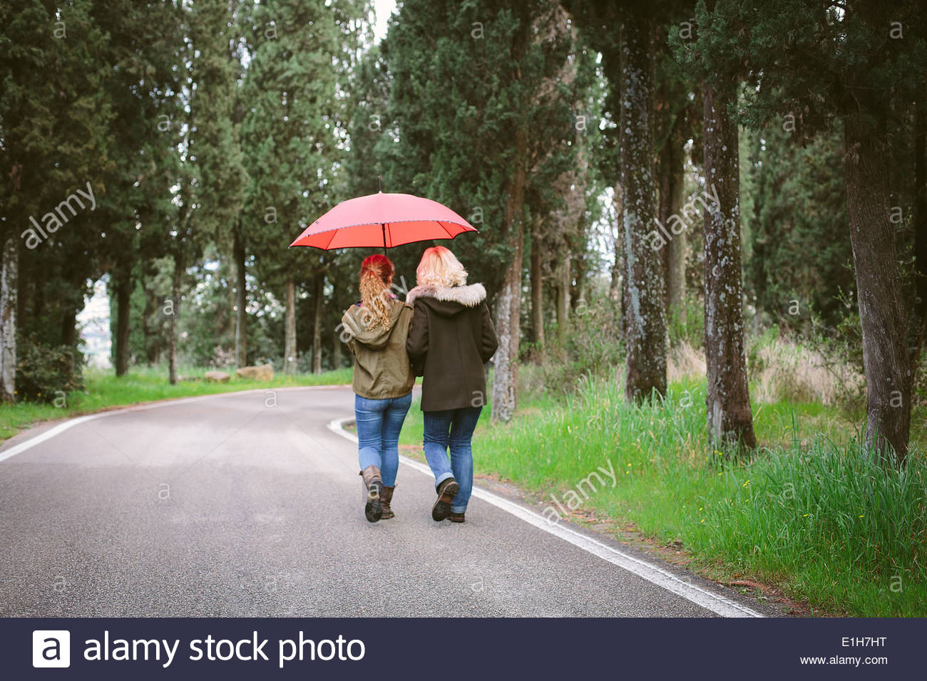 Rear view of mother and teenage daughter on rural road - Stock Image