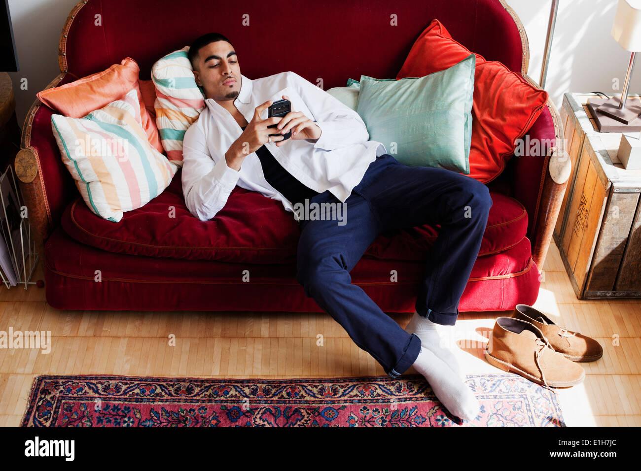 Young man lying on sofa, using smartphone - Stock Image