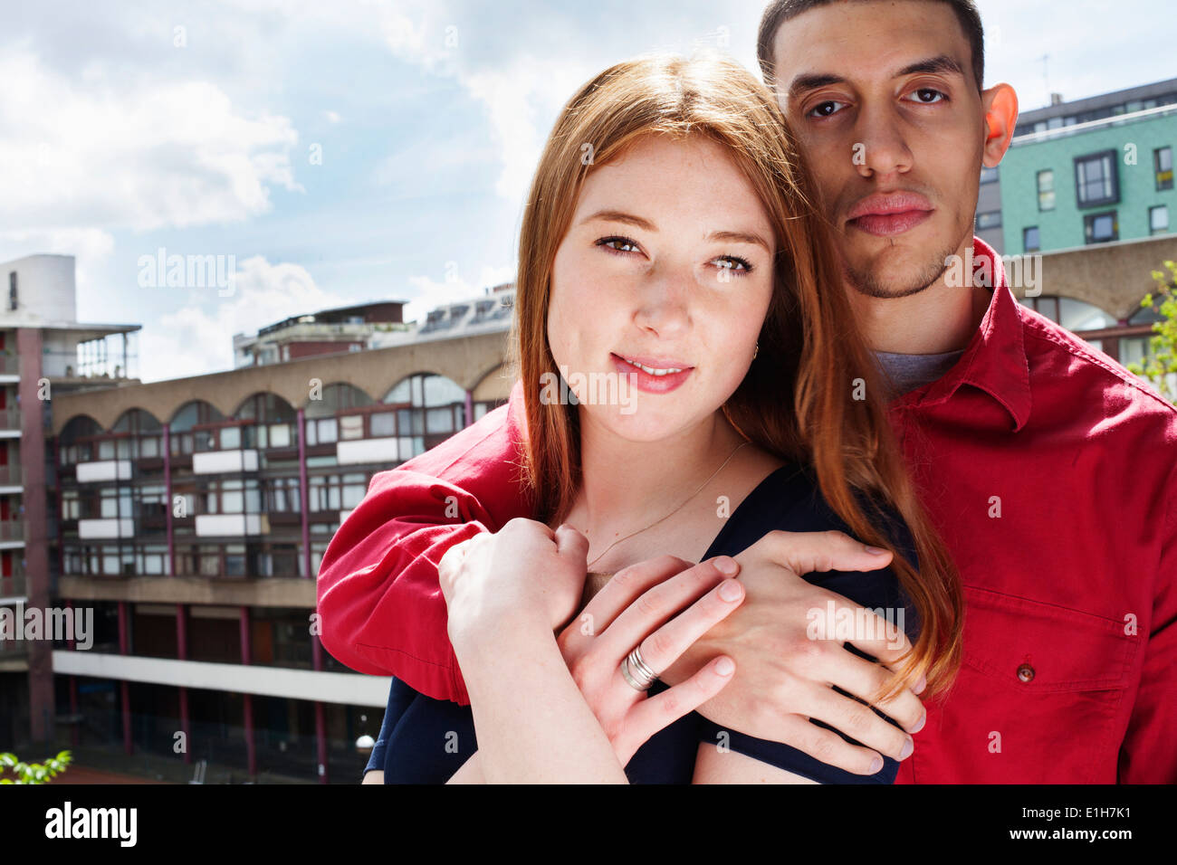 Young couple standing on balcony with arm around - Stock Image