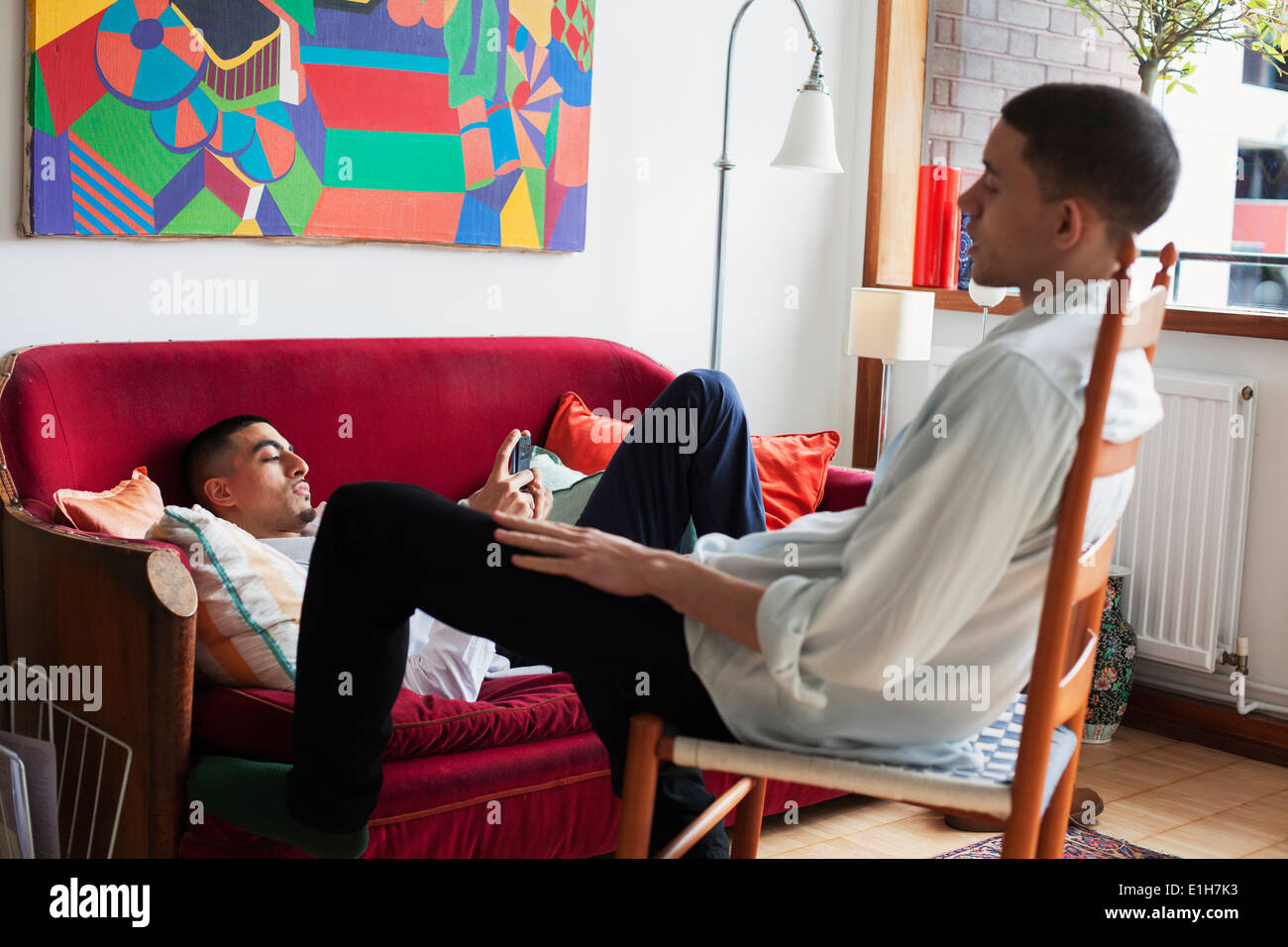 Young men relaxing in living room - Stock Image