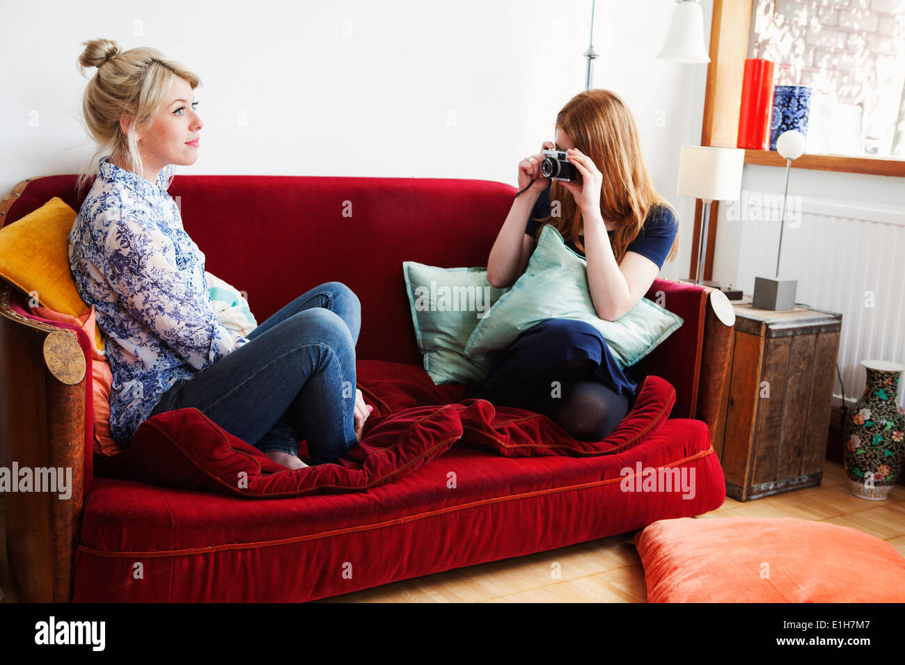 Young women sitting on sofa, taking photograph - Stock Image