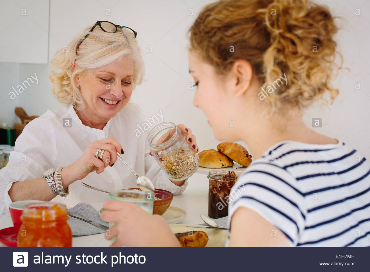 Mother and teenage daughter sharing breakfast at home - Stock Image