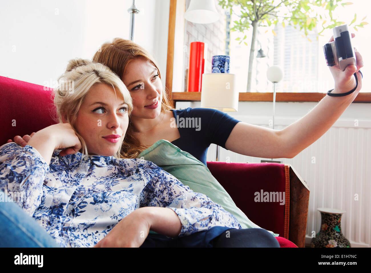 Young women sitting on sofa, taking self portrait photograph Stock Photo
