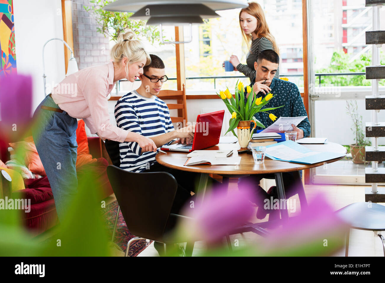 Four young adults sitting around table studying - Stock Image