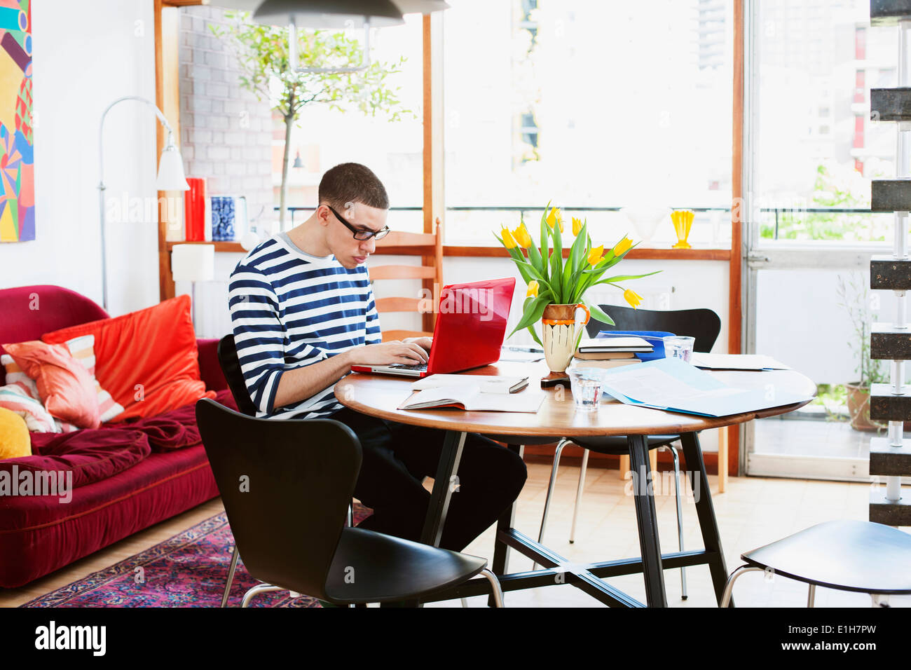 Young man sitting at table using laptop - Stock Image