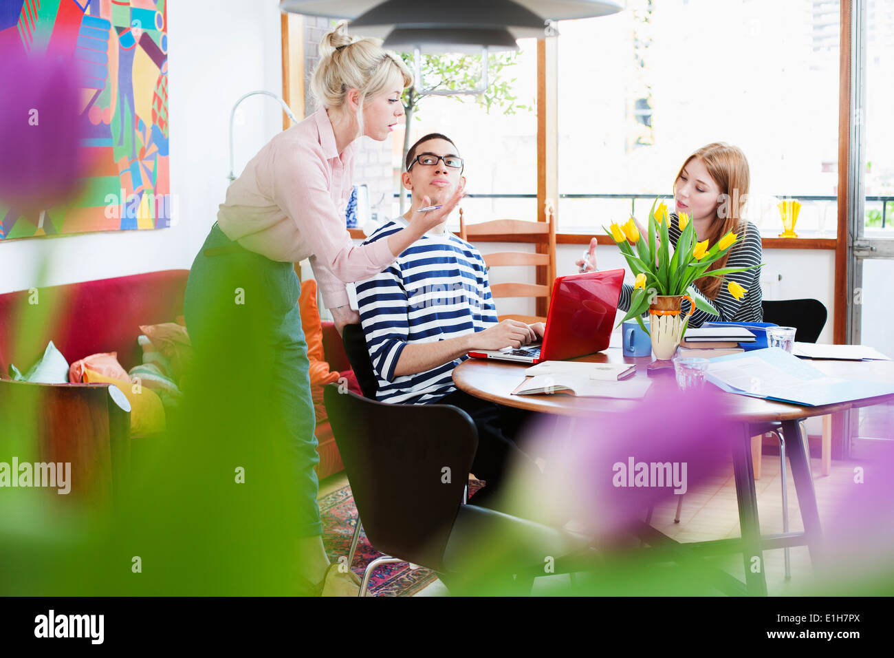 Young adults sitting around table studying - Stock Image