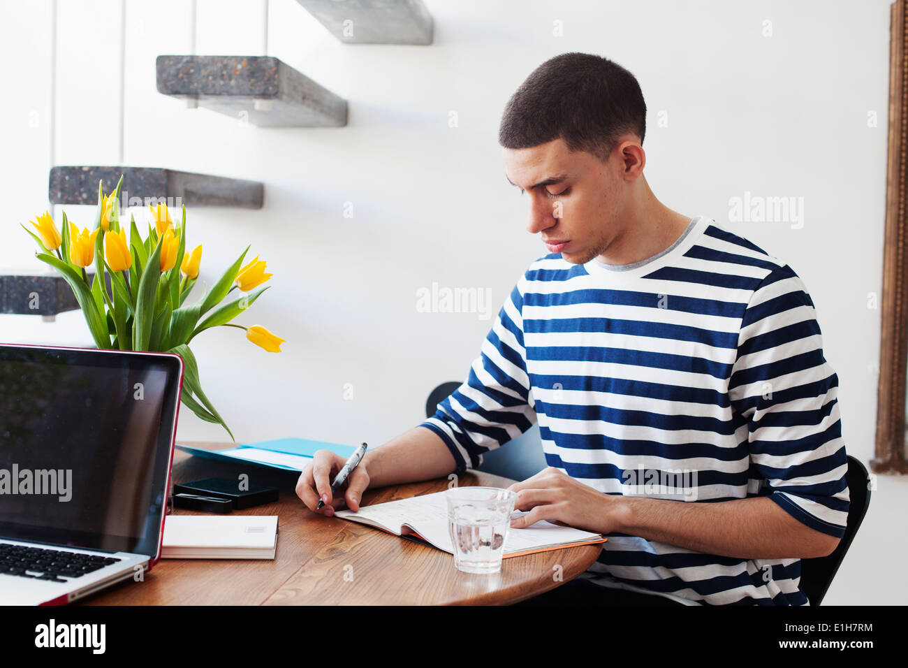 Young man sitting at table, writing in notebook - Stock Image