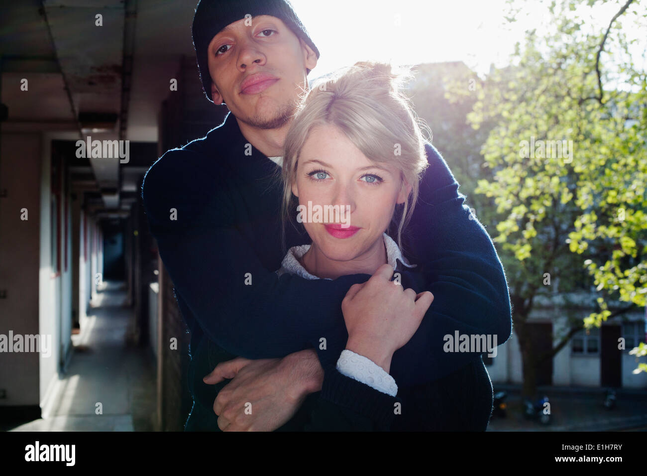 Young couple with arm around, standing in block of flats, London, UK - Stock Image