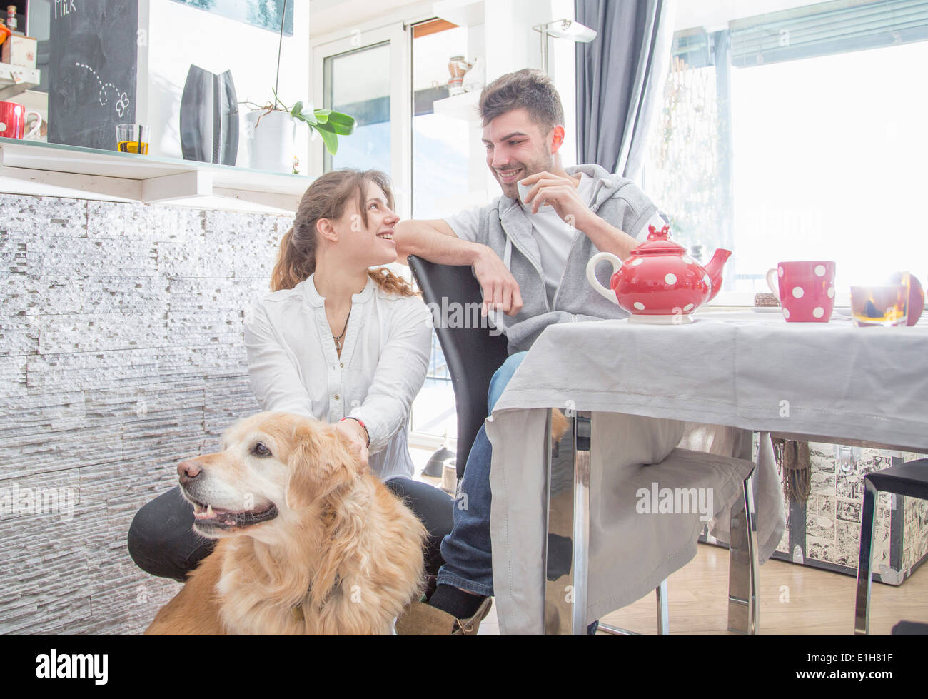 Young couple having breakfast, with dog - Stock Image