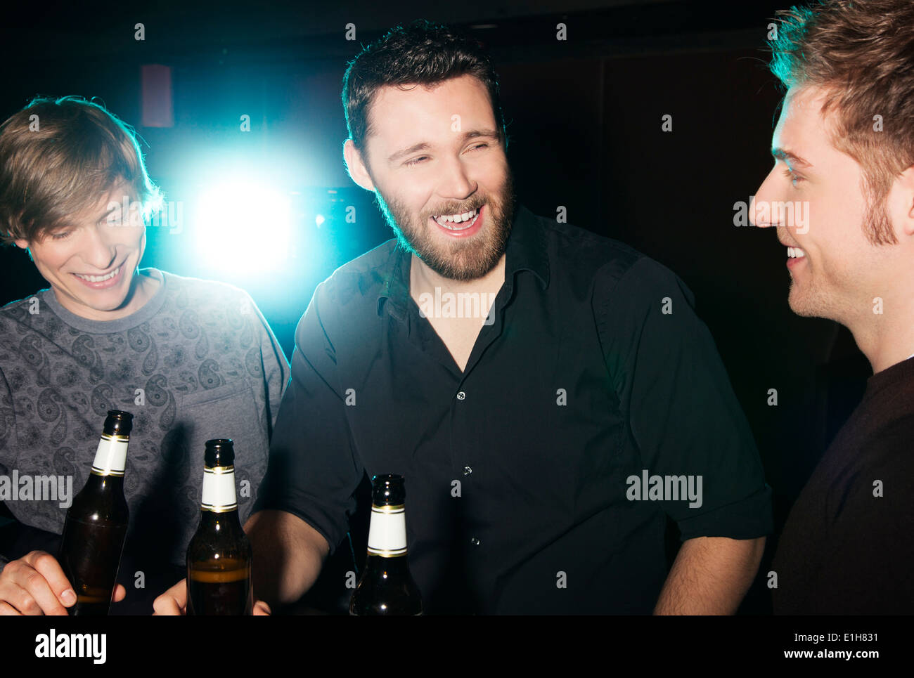 Three male friends drinking bottled beer in nightclub - Stock Image