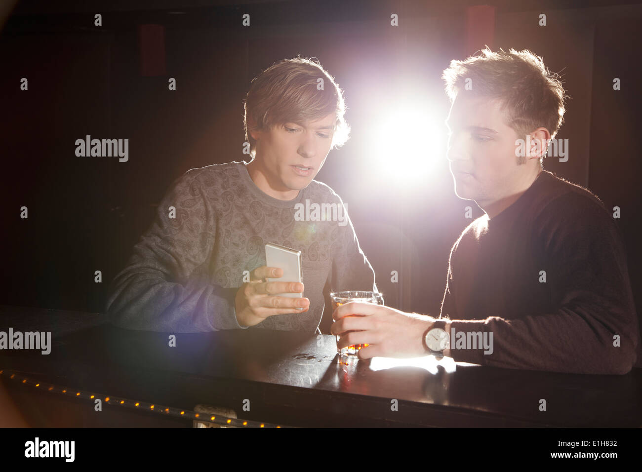 Two male friends looking at smartphone in nightclub Stock Photo