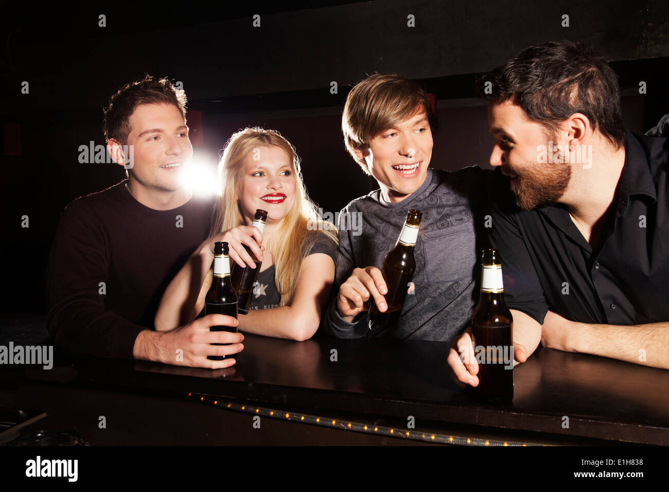 Four friends drinking bottled beer in nightclub - Stock Image