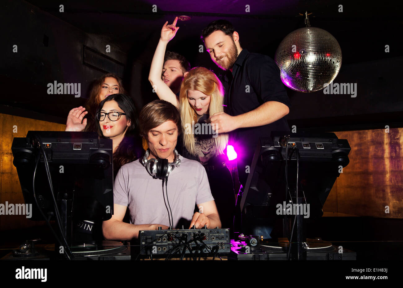 Group of friends watching DJ in nightclub Stock Photo