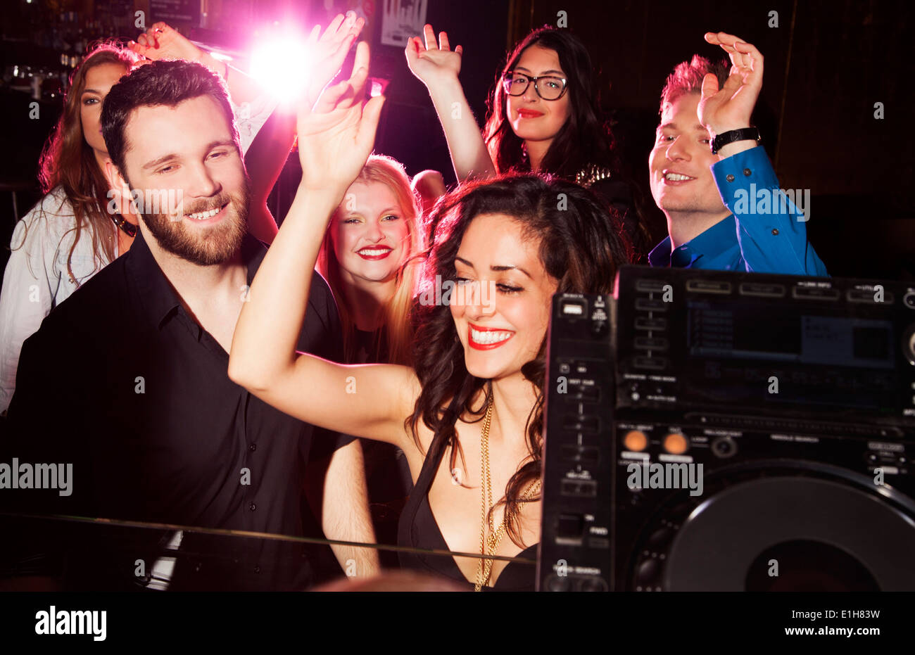 Group of young men and women dancing in nightclub - Stock Image