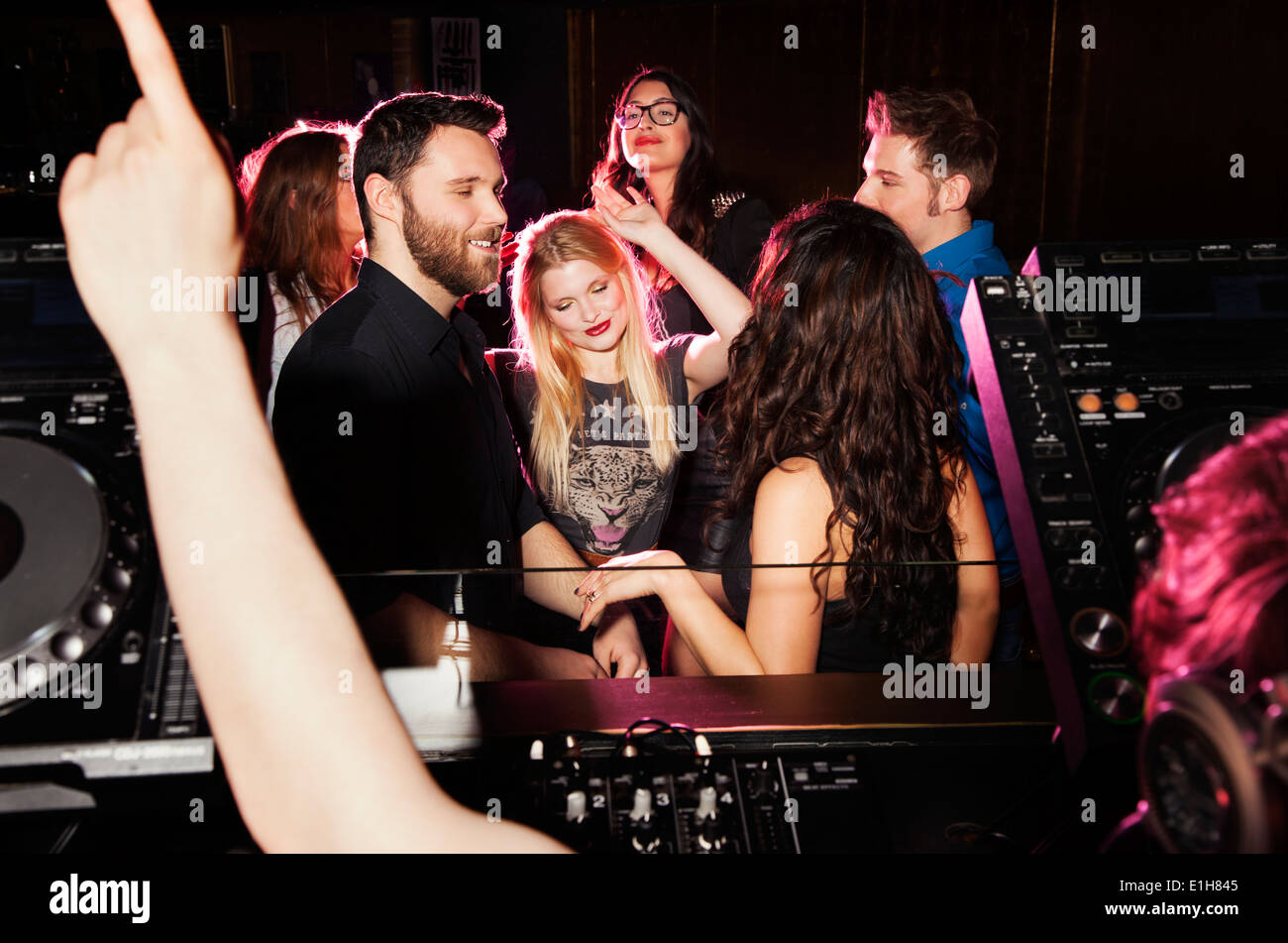 Group of young men and women dancing in front of DJ in nightclub - Stock Image