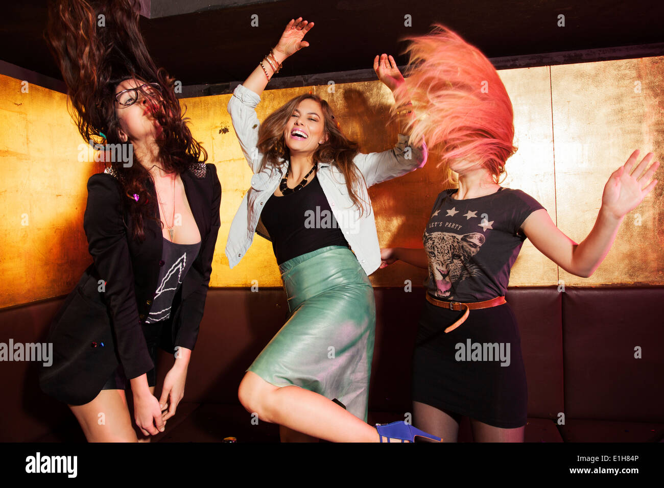 Four female friends dancing in nightclub - Stock Image