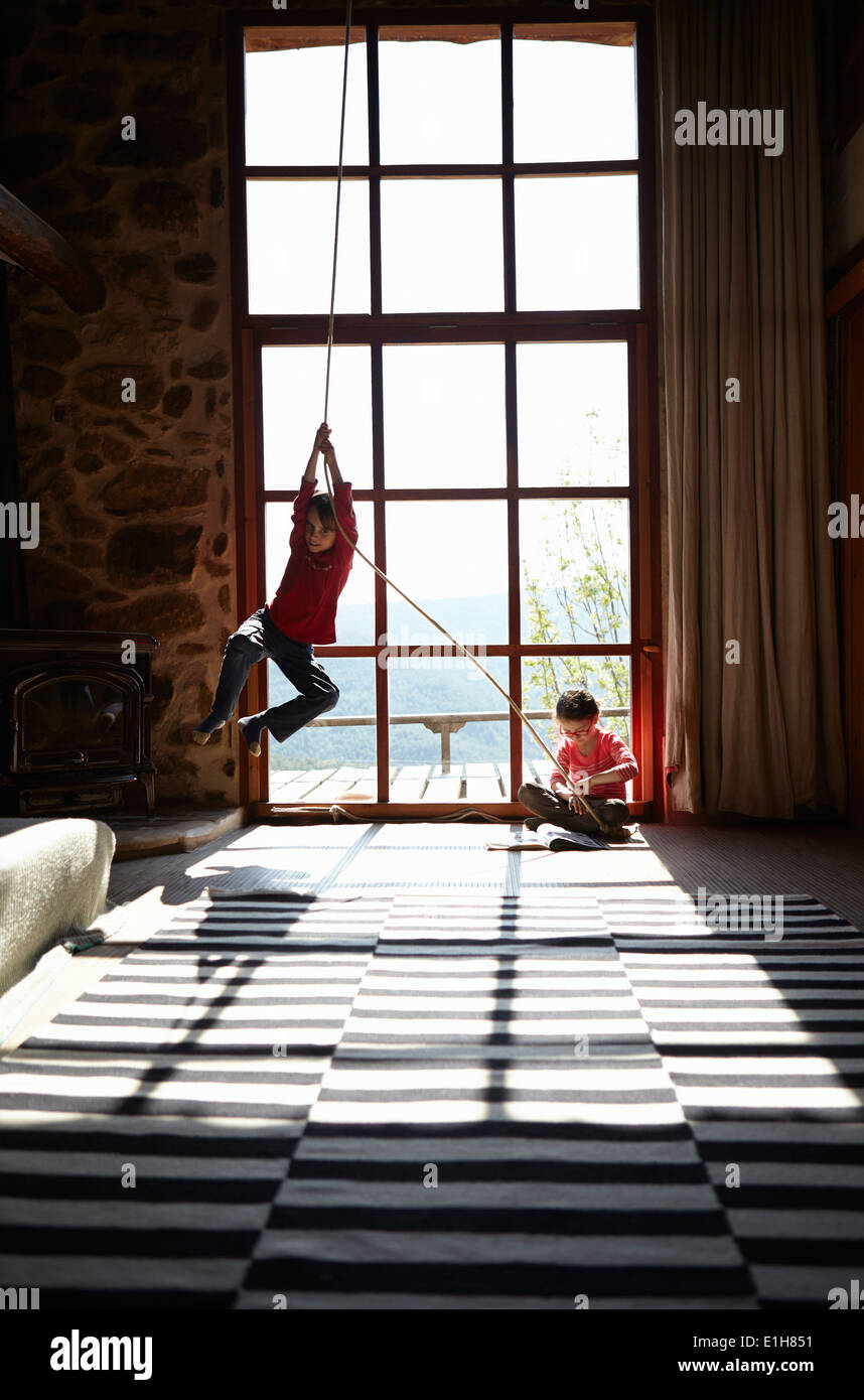 Two siblings in sitting room, brother on rope swing and sister reading - Stock Image