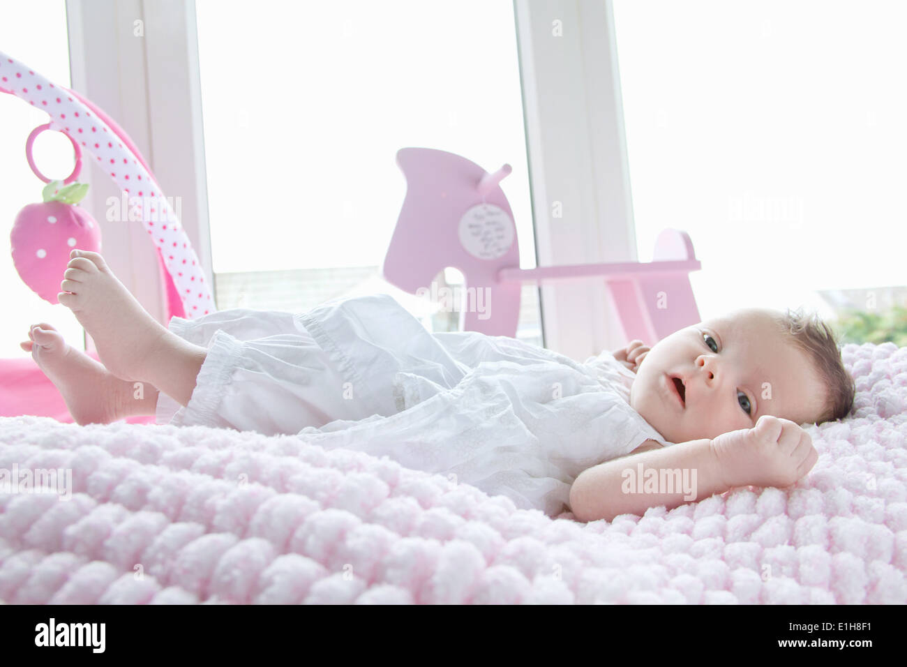 Baby girl lying in bed - Stock Image