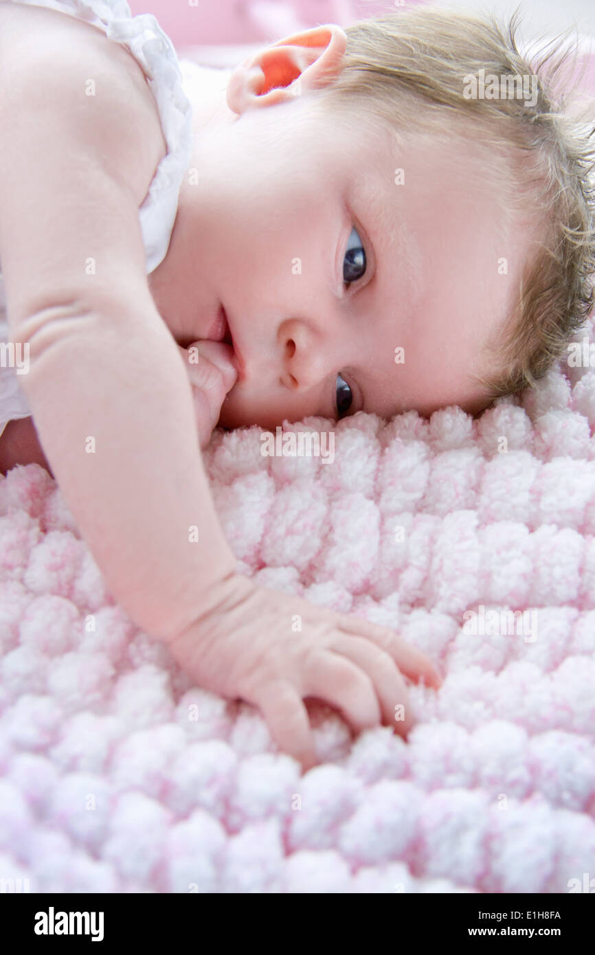 Baby girl lying on side sucking finger - Stock Image