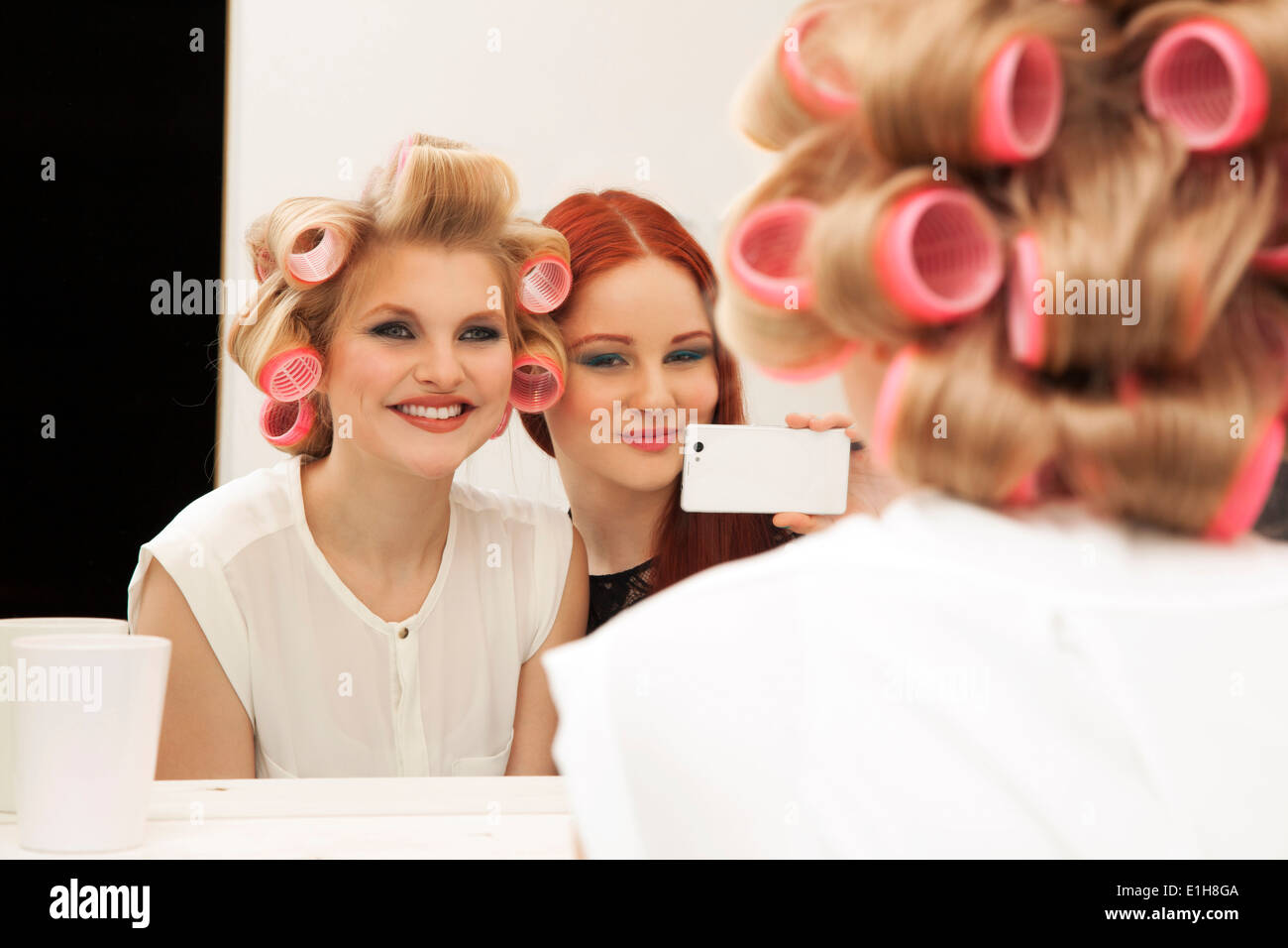 Young woman in curlers and friend taking selfie Stock Photo