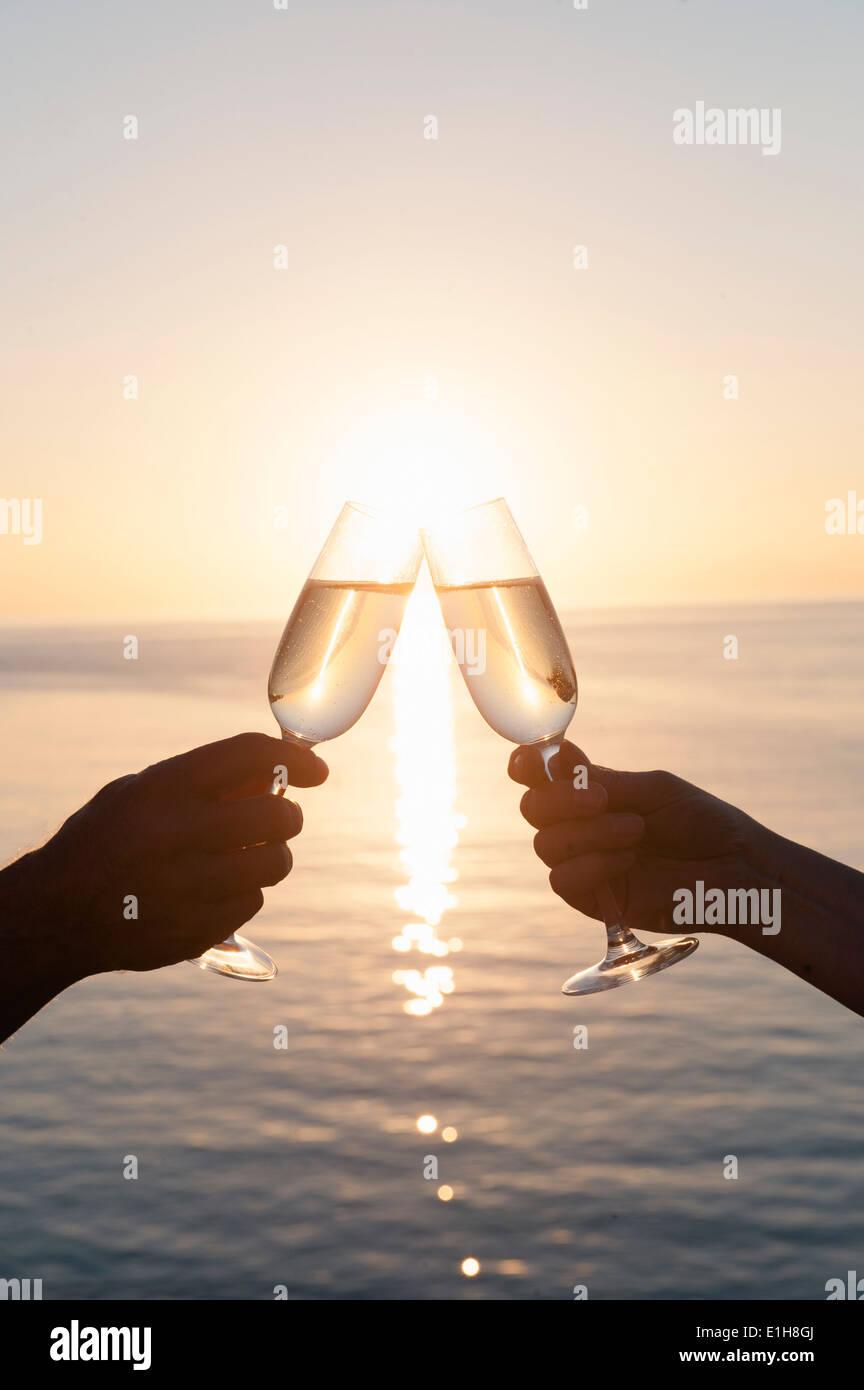 Couple toasting against sunset - Stock Image