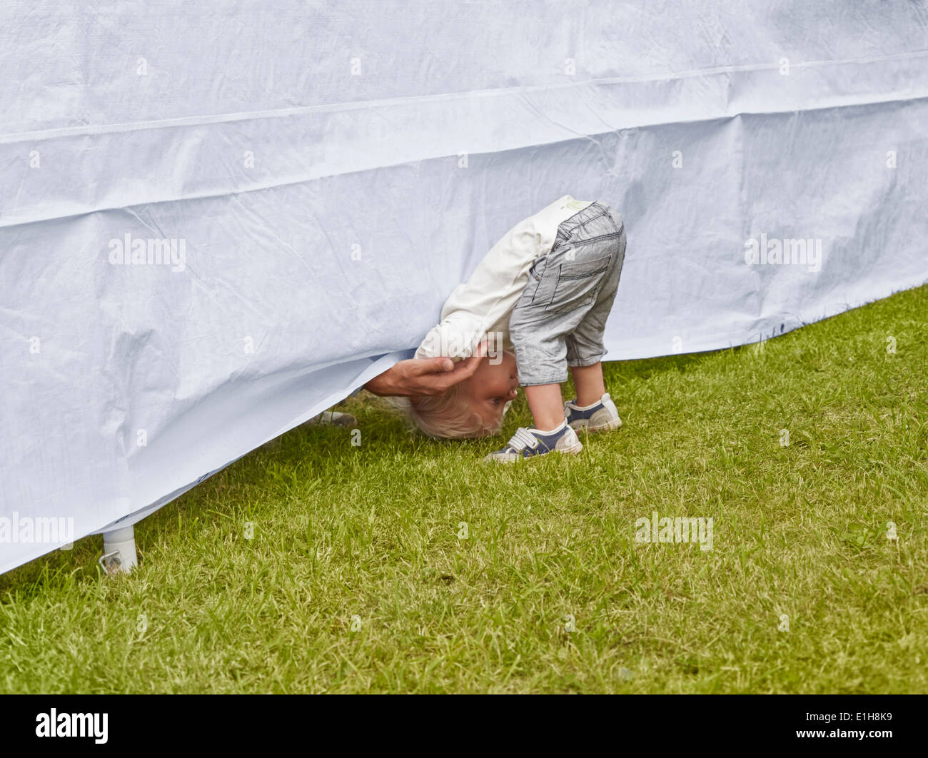 Young boy bending forward to reach fathers hand under tent - Stock Image