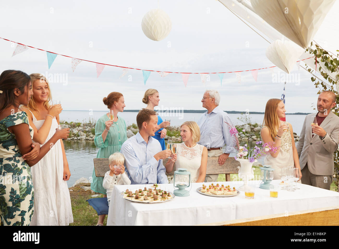 Mid adult couple making a toast with friends at wedding reception - Stock Image