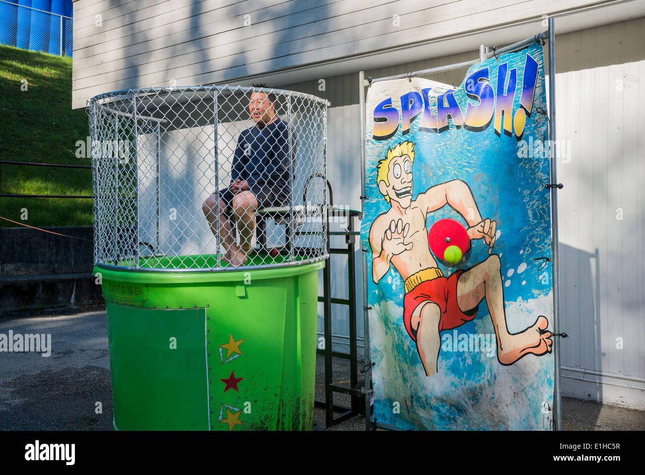 Ball hits button of dunk tank. - Stock Image