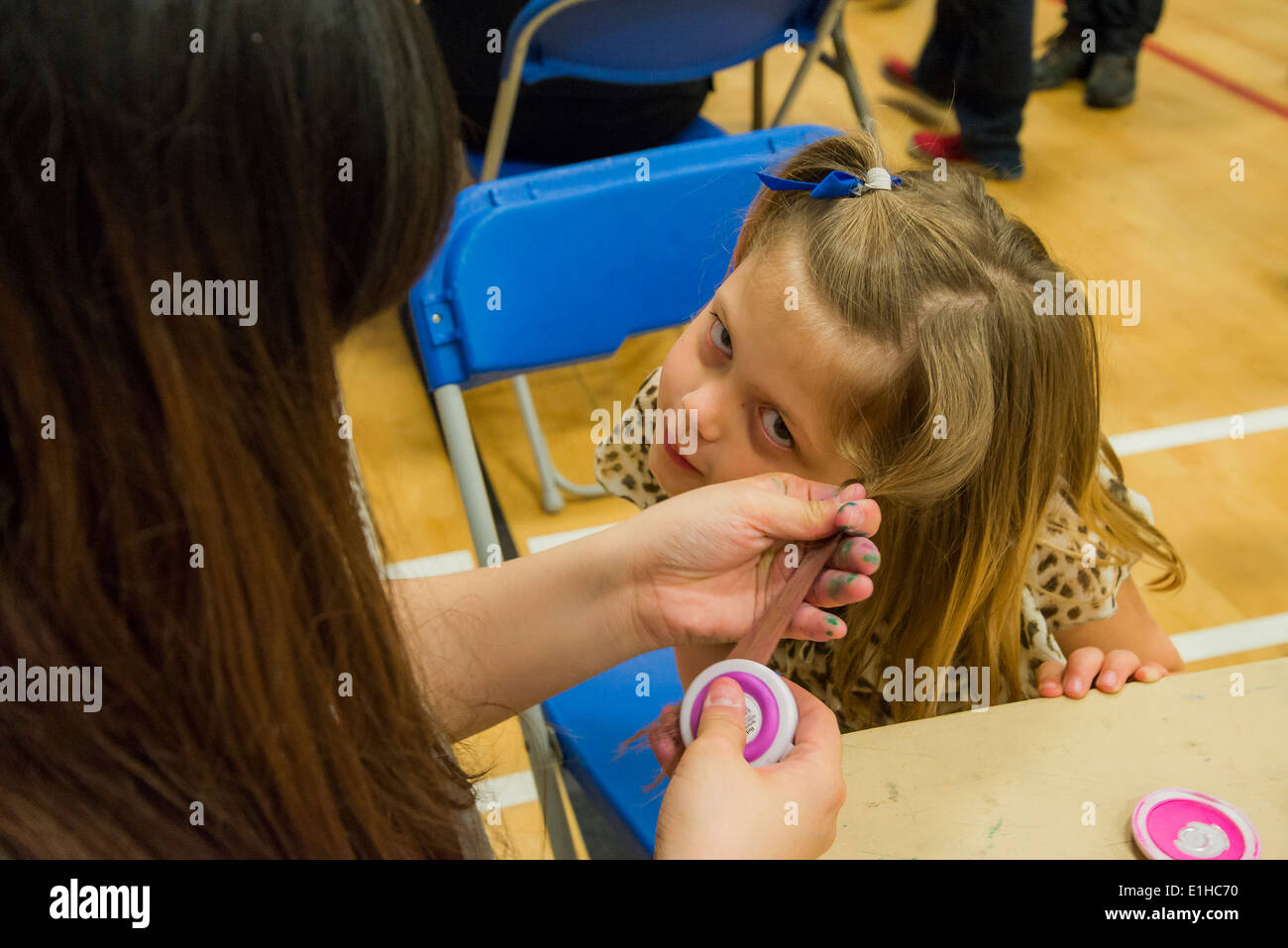 Young girl gets temporary hair chalk applied at Spring Fair, Burnaby, British Columbia, Canada - Stock Image