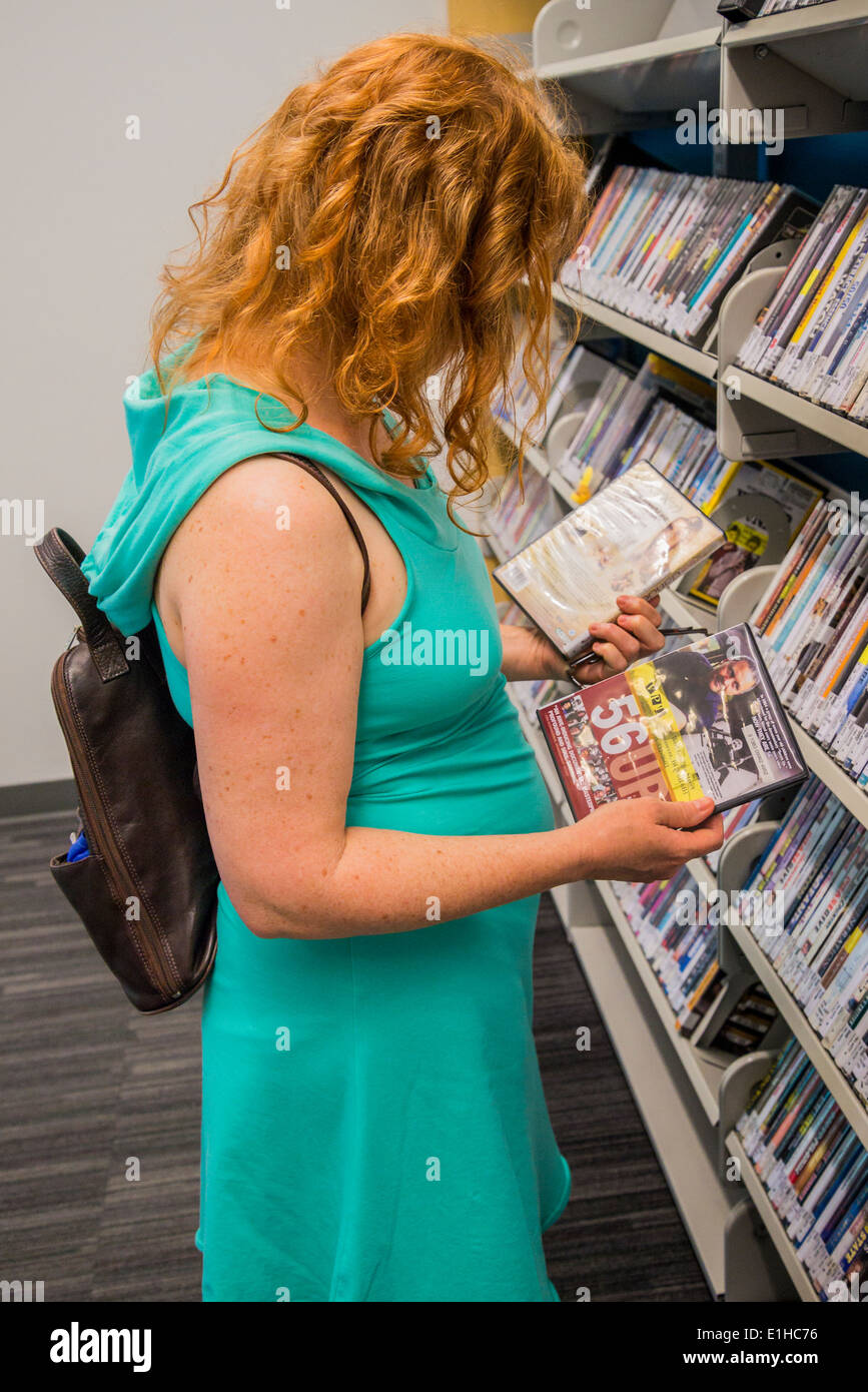 Woman browses dvd's on library shelves - Stock Image
