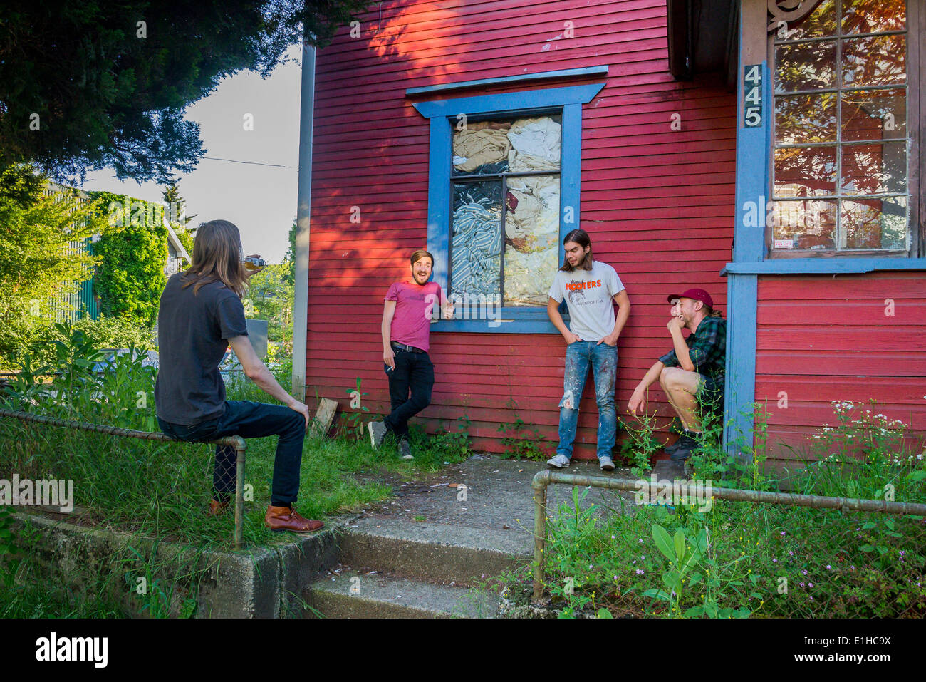 Guys hanging out in the front yard, Strathcona neighbourhood, Vancouver, British Columbia, Canada - Stock Image
