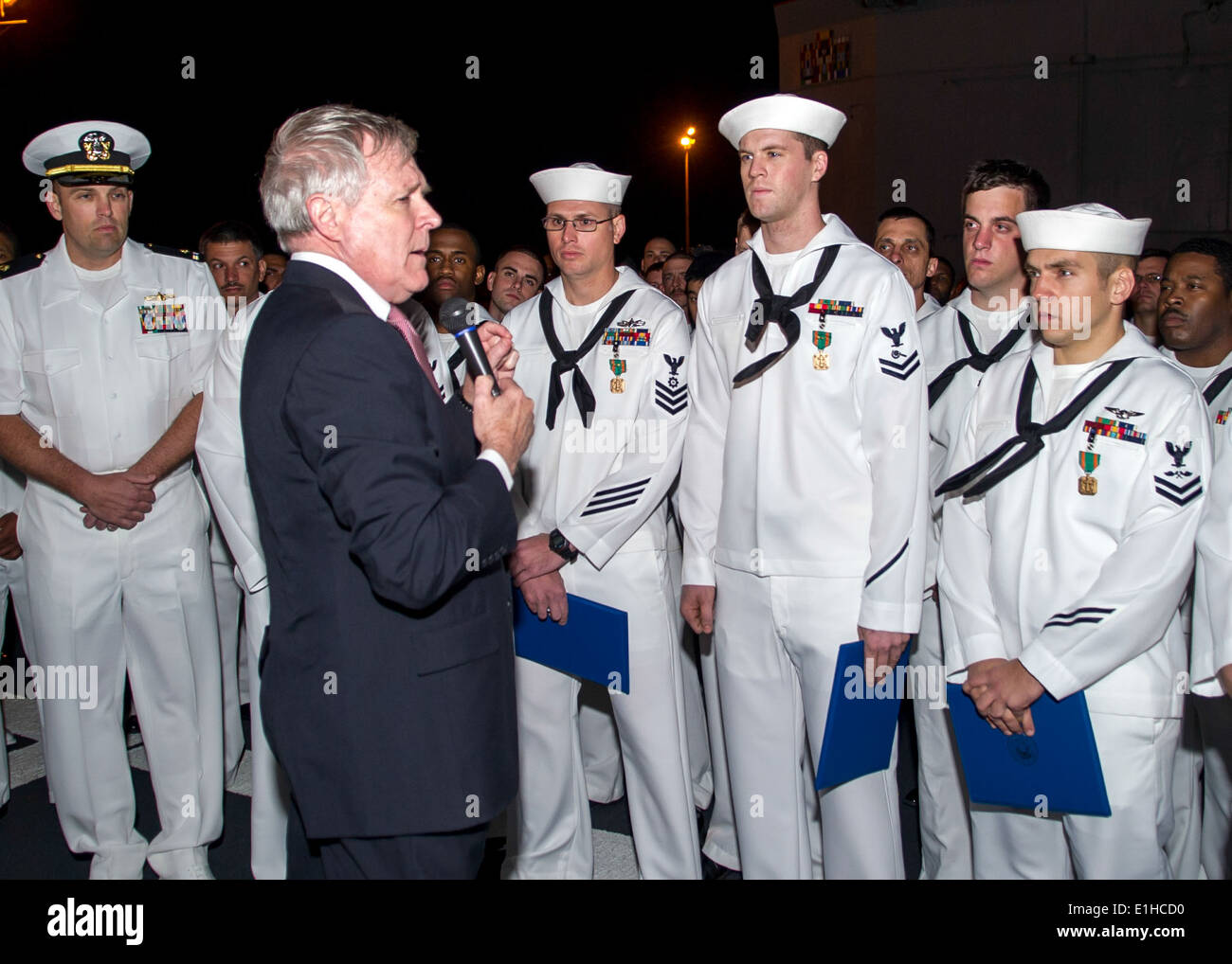 Secretary of the Navy Ray Mabus, second from left, speaks with U.S. Sailors during an all-hands call aboard the Stock Photo