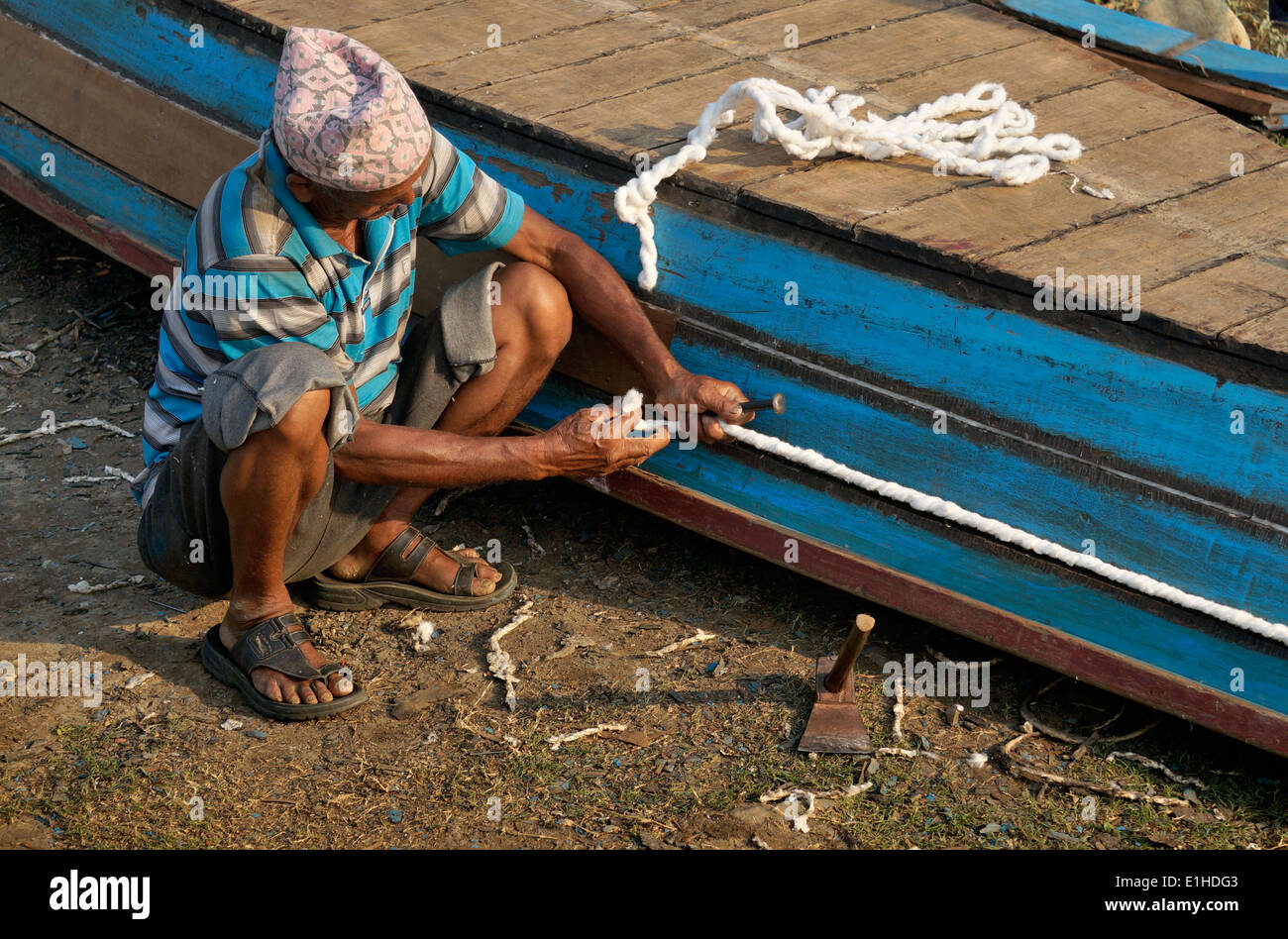 Man is fixing his wooden boat - Stock Image